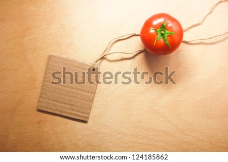 tomato vegetable and price tag on wood background texture