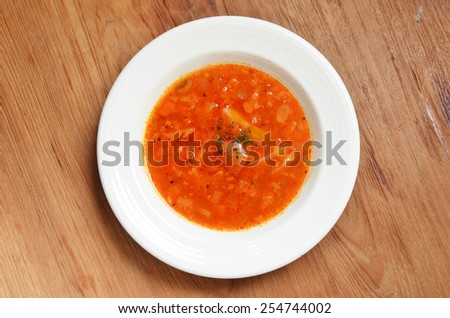 Tomato vegetable soup on wooden table  - stock photo