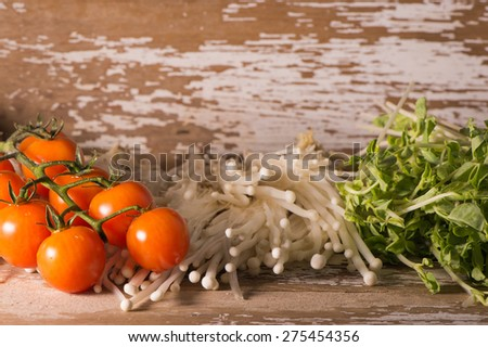 Tomato with Pea Sprout and Golden needle mushroom on wood top - stock photo