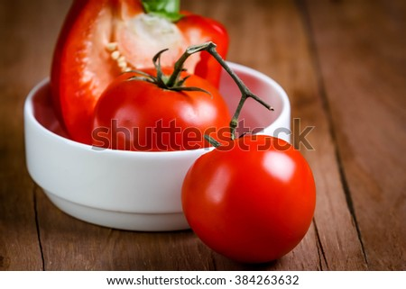 tomato with pepper bell in cup on wooden - stock photo