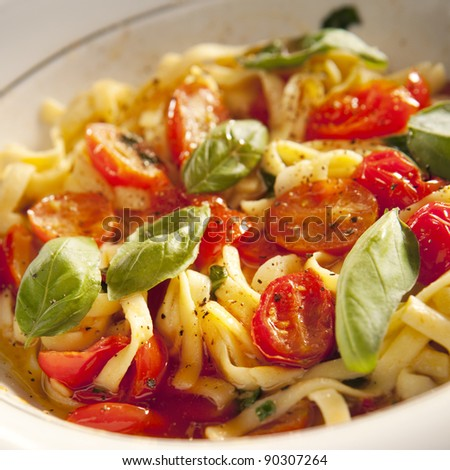 Tomatoa pasta on plate with fresh basil leaves - stock photo