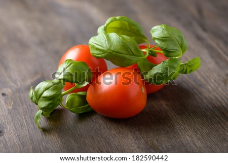 Tomatoes and basil on a wood table - stock photo