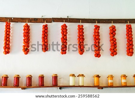 Tomatoes and canned food on wooden shelf. - stock photo
