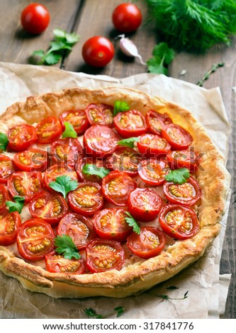 Tomatoes and cheese tart on wooden table - stock photo