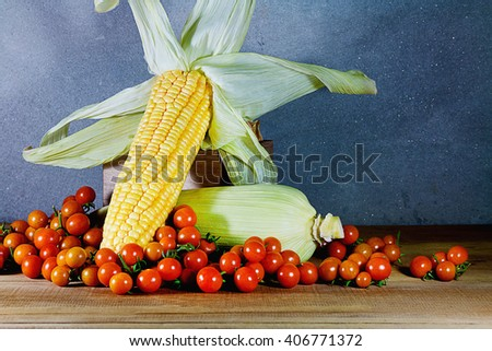 tomatoes and corn on the wooden table - stock photo