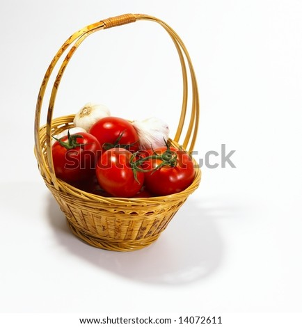 Tomatoes and garlic in basket on white background
