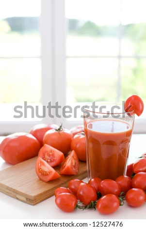 Tomatoes and glass of fresh tomato juice. - stock photo