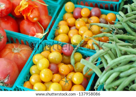tomatoes and green beans in small buckets at market - stock photo