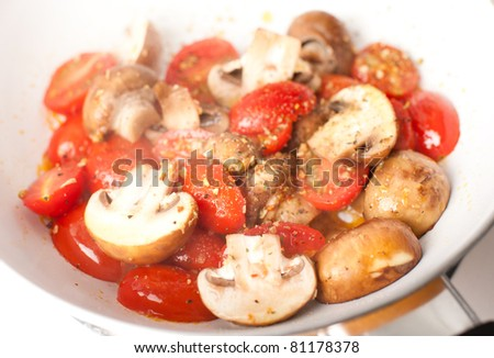 Tomatoes and Mushrooms Sauteed with Herbs and Spices in Enameled Pan - stock photo