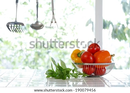 Tomatoes and peppers are placed in a basket next to fresh herbs. - stock photo