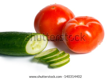 Tomatoes and sliced cucumber on a white background
