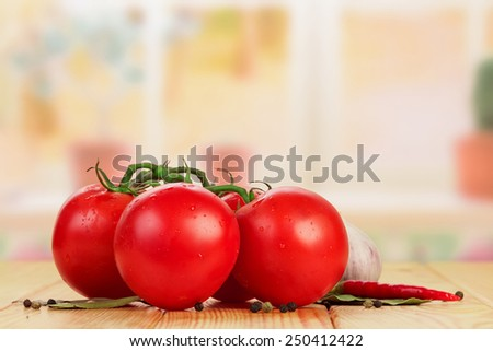 Tomatoes and spices on light wooden table - stock photo