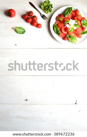 Tomatoes,cottage cheese and basil leaves salad on the white wooden background - stock photo