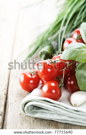 Tomatoes, garlic, chives and chili peppers on a wooden table top - stock photo