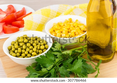 Tomatoes, green peas, sweet corn, parsley and olive oil on board - stock photo
