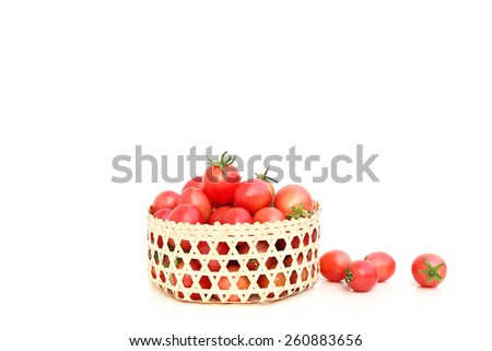 Tomatoes in bamboo handcraft basket isolated in white background - stock photo