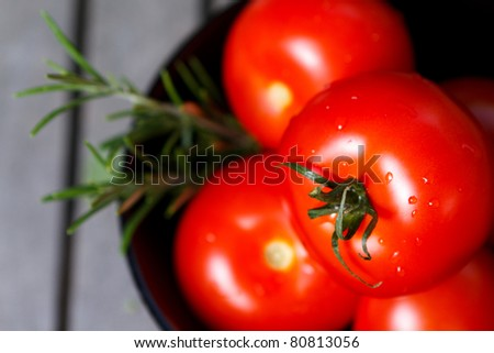 Tomatoes in black bowl with herbs - stock photo