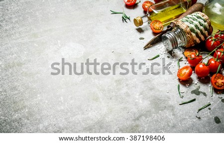 Tomatoes in the background. Fresh tomatoes, olive oil and spices. On a stone background.  - stock photo