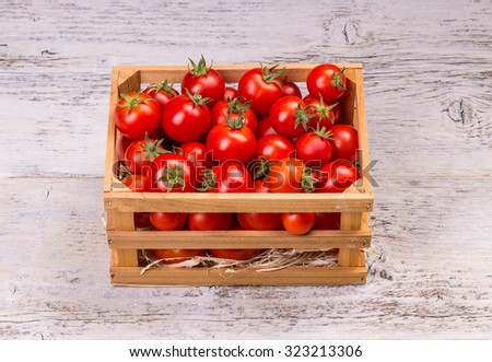 Tomatoes in wooden crate on white wooden board