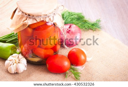 Tomatoes marinated in a jar with spices and vegetables on a wooden table - stock photo