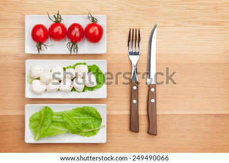 Tomatoes, mozzarella, green salad leaves and silverware on wooden table with copy space - stock photo