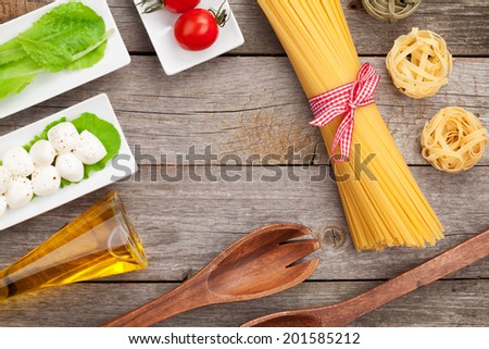 Tomatoes, mozzarella, pasta and green salad leaves on wooden table background - stock photo