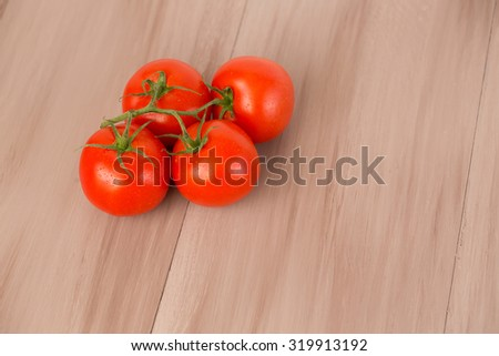 Tomatoes on a branch on a wooden background.