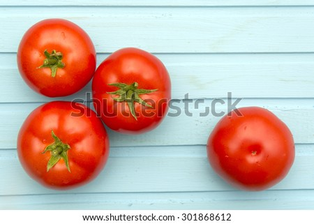 Tomatoes on blue wooden background  - stock photo