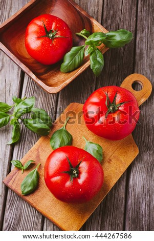 Tomatoes on cutting board and bowl with basil - stock photo