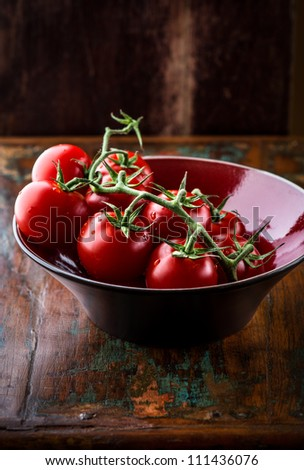 Tomatoes on the vine in ceramic bowl - stock photo