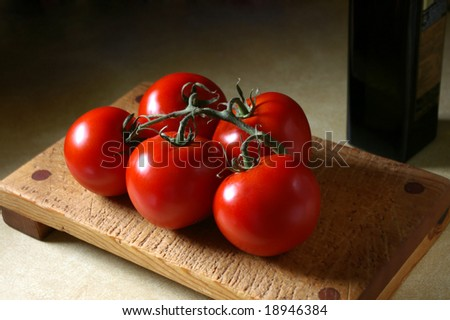 Tomatoes on the vine, on cutting board in kitchen setting - stock photo
