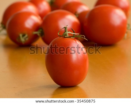 Tomatoes on the wooden table. Shallow DOF.