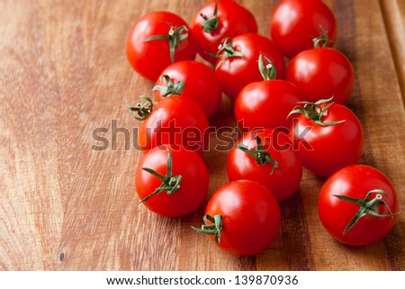 Tomatoes on wooden cutting board. selective focus, shallow dof - stock photo