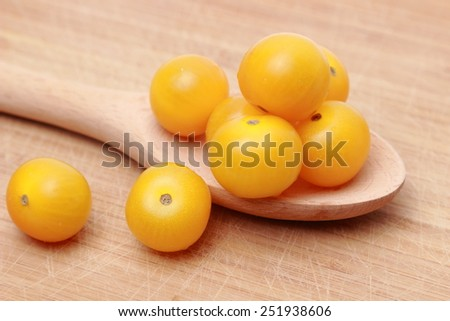 tomatoes over wooden spoon - stock photo