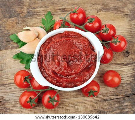 Tomatoes paste with spices and greens on wooden tables - stock photo
