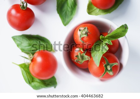 Tomatoes. red ripe tomatoes and basil leaves. - stock photo