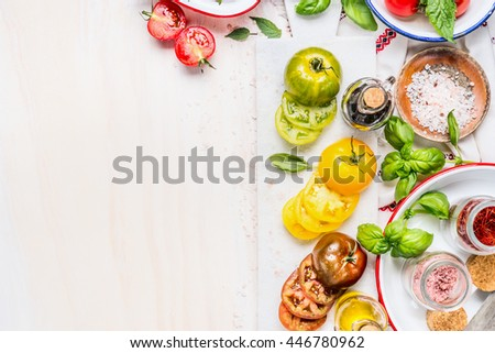 Tomatoes salad preparation. Tomatoes cooking ingredients on white marble cutting board. Various Colorful sliced tomatoes on white wooden background, top view, place for text, border