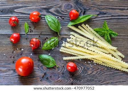 Tomatoes with basil and pasta  in colander on wooden table background. Food composition. Top view