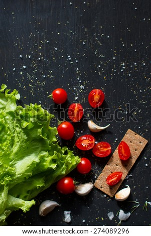 Tomatoes with lettuce leaves and a slice of bread on a dark wooden background - stock photo