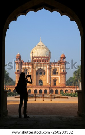 Tomb of Safdarjung seen from main gateway with silhouetted person taking photo, New Delhi, India. It was built in 1754 in the late Mughal Empire style. - stock photo