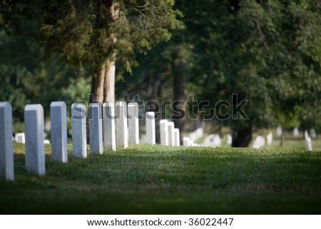 tombs at Arlington Cemetery in Washington DC (with the Memorial for J.F. Kennedy) - stock photo