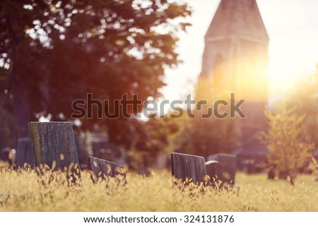 Tombstone and graves in a church graveyard in the fall - stock photo