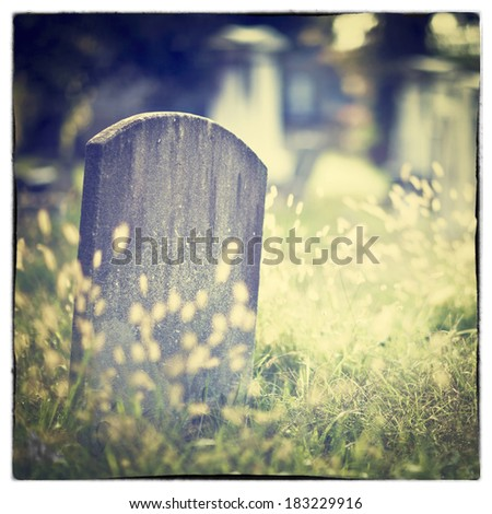 Tombstone and graves in an ancient church graveyard with Instagram style filter effect - stock photo