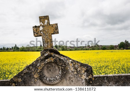 tombstone cross against oilseed rape fields, Pontigny, Burgundy, France - stock photo