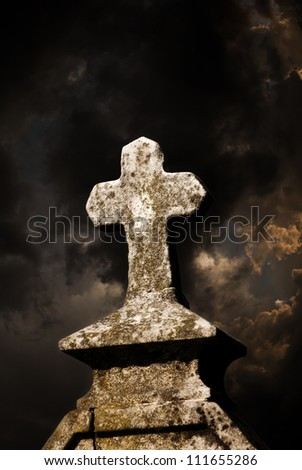 tombstone cross and dark sky - stock photo