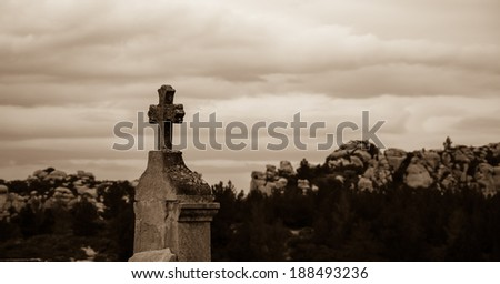 Tombstone with the cross at the old cemetery in Les Baux-de-Provence (Provence, France). Aged photo. Sepia. - stock photo