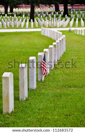 tombstones on a national cemetery with the american flag - stock photo