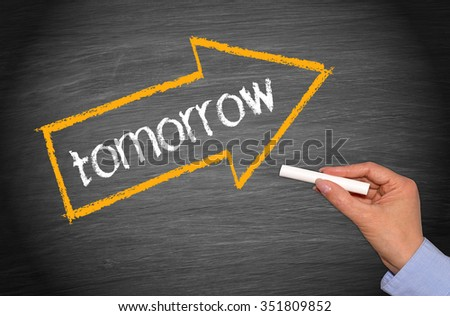 tomorrow arrow with text and female hand with chalk on blackboard - stock photo