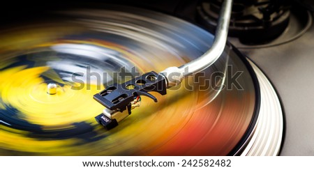 Tonearm on a spinning color picture vinyl. - stock photo
