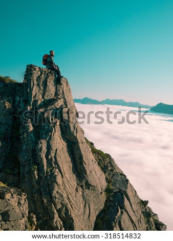 Toned image adult man with backpack sitting, legs dangling on the edge of a cliff and looks into the distance against the blue sky and thick clouds floating down - stock photo